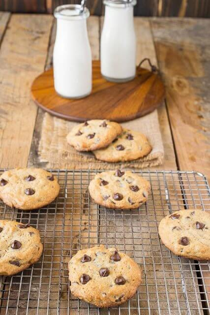 Peanut Butter Chocolate Chip Cookies on a cooling rack with two glasses of milk.