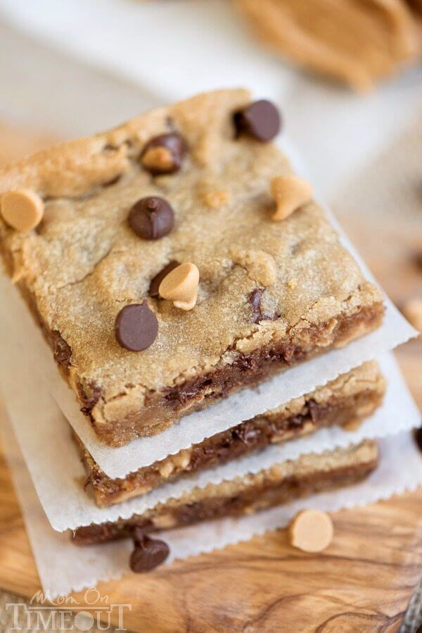 Peanut Butter Chocolate Chip Brownies stacked up on parchment paper.