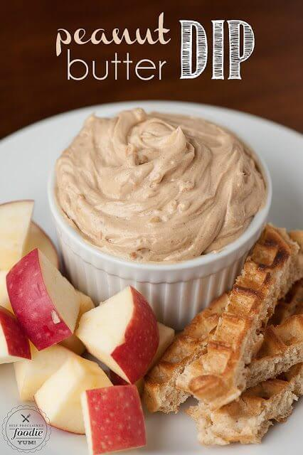 Peanut Butter Dip in a bowl with apple slices and bread sticks on a plate.