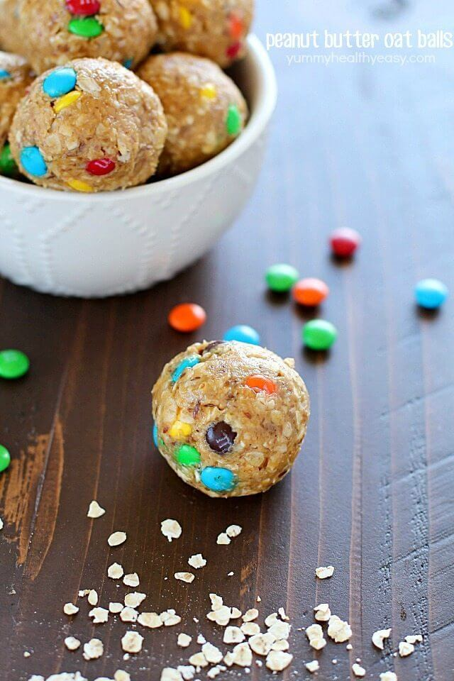 Peanut Butter Oat Balls in a bowl and one ball on the table with M&M candies.