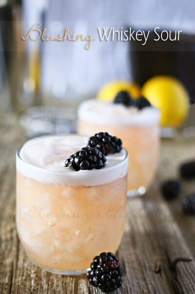 Blushing Whiskey Sour in two glasses with black berries.