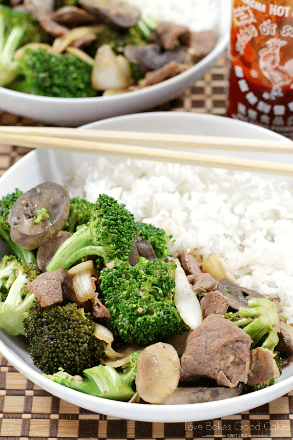 Slow Cooker Beef & Broccoli on a plate with rice with chop sticks.