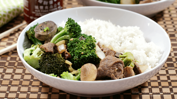 Slow Cooker Beef & Broccoli in a white bowl with white rice.