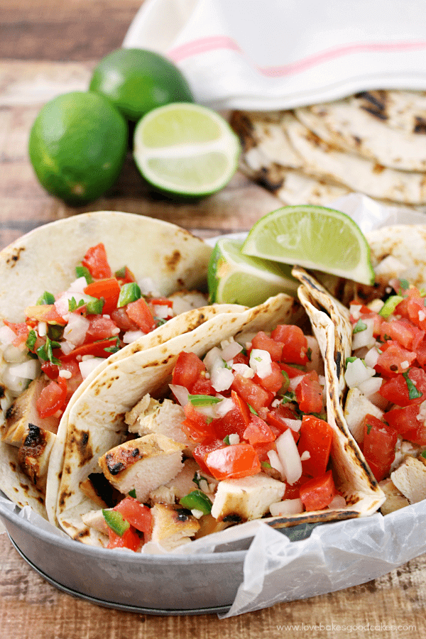 Grilled Chicken Fresco Tacos in a metal bowl with fresh limes.