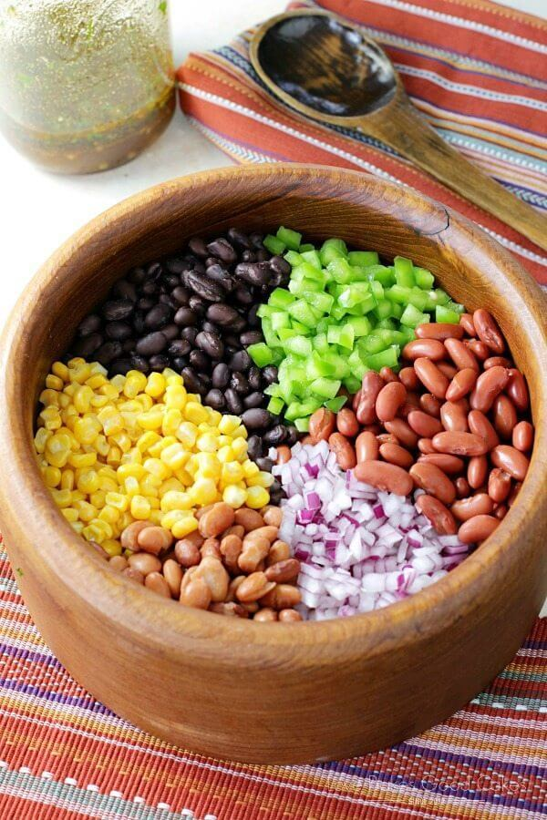 Mexican Bean Salad ingredients in a bowl with a spoon.