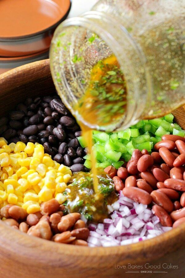 Mexican Bean Salad in a bowl with dressing being poured over it.