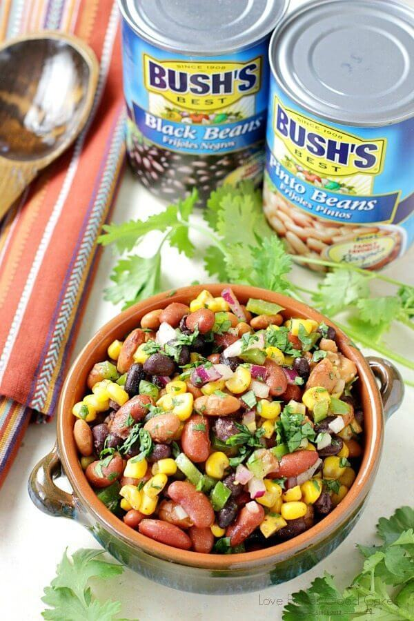 Mexican Bean Salad in a bowl with two cans of Bush's Beans and a spoon.