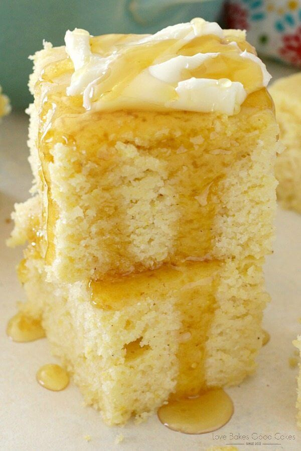 Southern Cornbread stacked up on a plate with butter and honey drizzle close up.