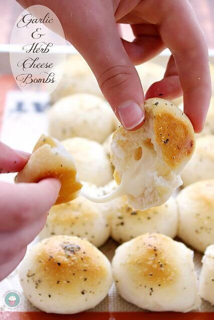 Garlic & Herb Cheese Bombs with cheese inside in someone's hands.