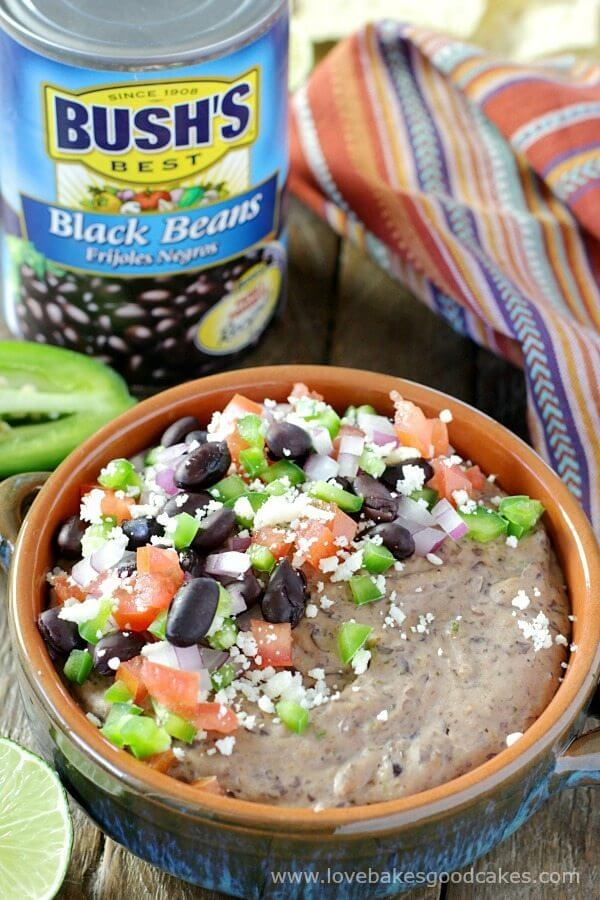 Loaded Mexican Black Bean Hummus in a bowl with a can of Bush's Black Beans.