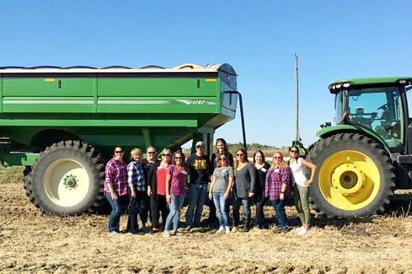 bloggers in front of farm equipment.