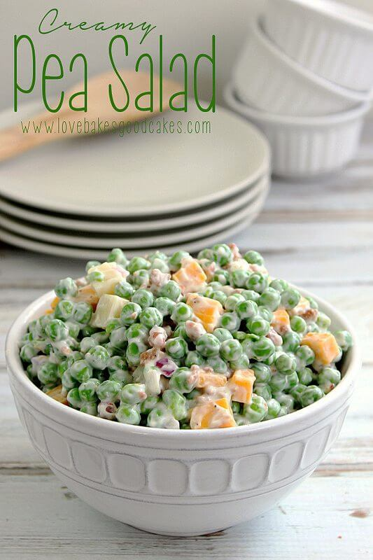 Creamy Pea Salad in a white bowl with a stack of plates.