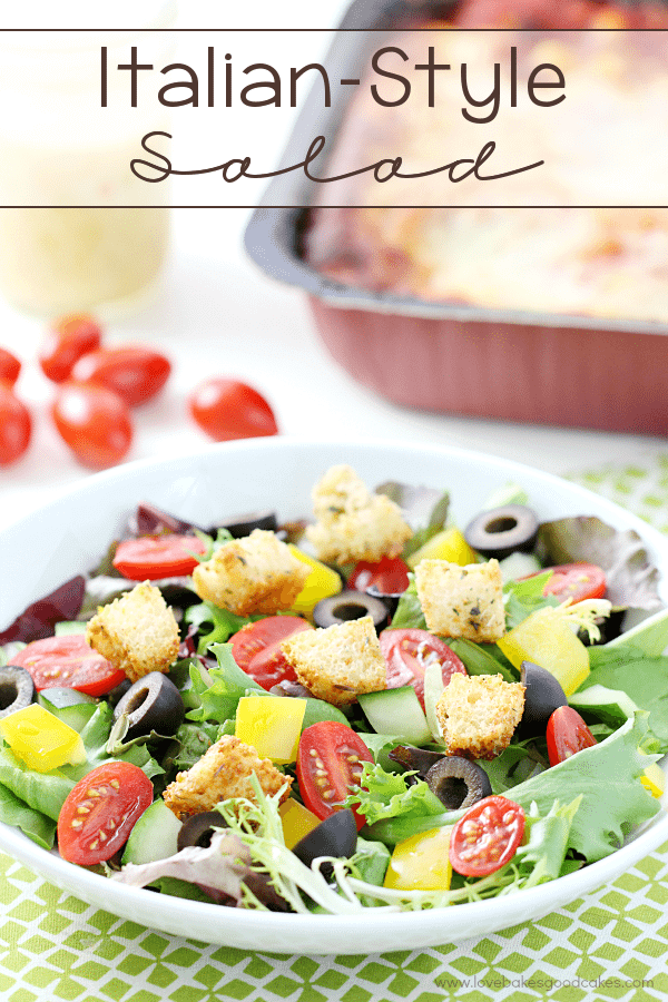 Italian-Style Salad in a white bowl with fresh tomatoes.