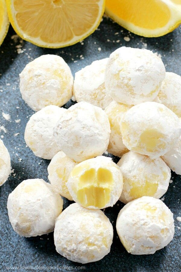 White Chocolate Lemon Truffles piled up on a plate with fresh lemons.