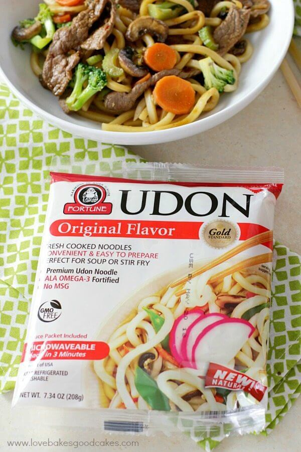 Hoisin Beef Noodle Stir Fry in a white bowl and a package of Udon noodles.