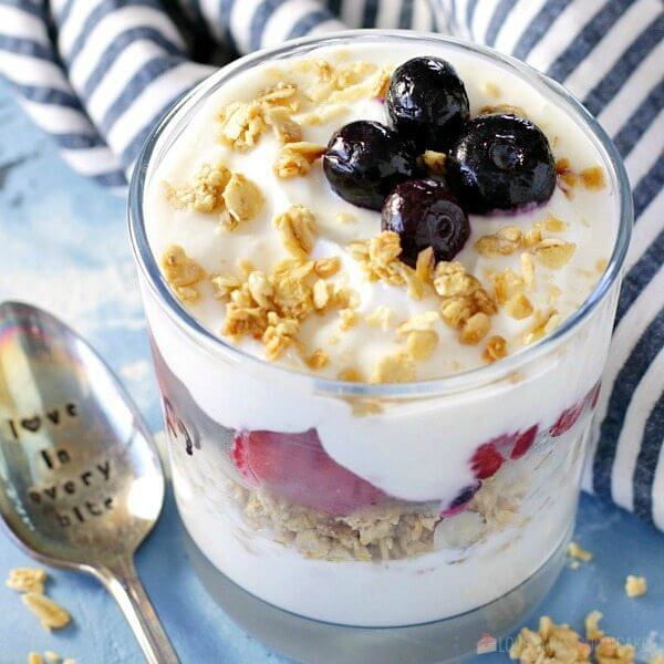 Fruit and Yogurt Breakfast Parfait in a glass with a spoon close up.