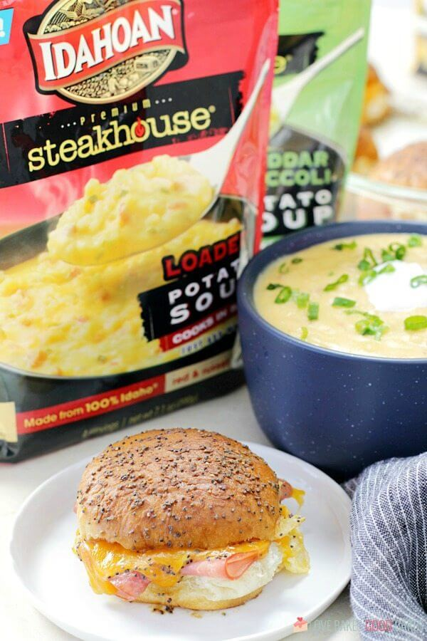Ham and Cheese Slider on a plate with a bowl of baked potato soup and two packages of Idahoan soup mix.