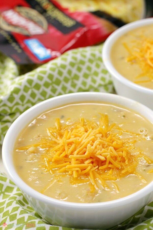 Two bowls of baked potato soup with shredded cheese on top.