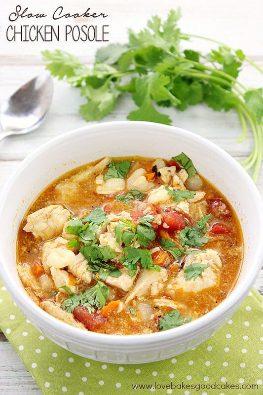 Slow Cooker Chicken Posole in a white bowl with cilantro and a spoon.