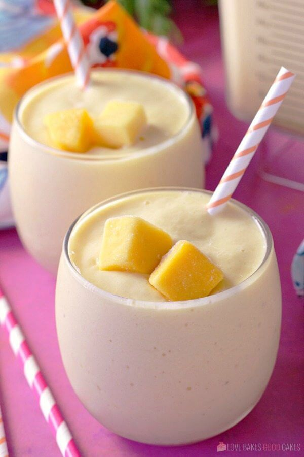 Sunshine Smoothie with Banana and Mango in two glasses with straws close up.
