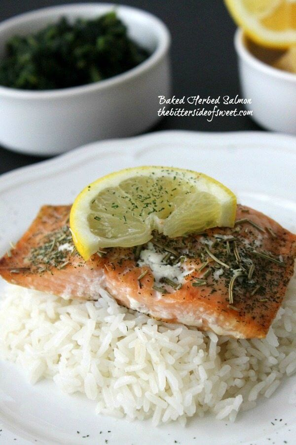 Baked Herbed Salmon with rice on a plate with a lemon slice.