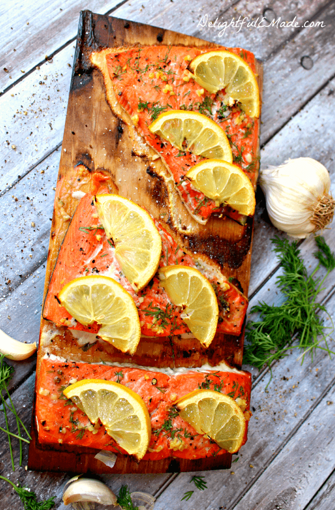 Grilled Cedar Plank Salmon with lemon slices on a cutting board.
