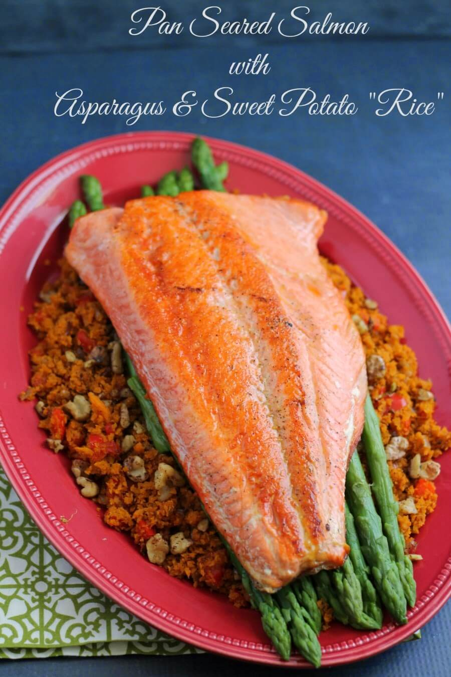"Pan Seared Salmon with Asparagus & Sweet Potato ""Rice"" on a red plate."
