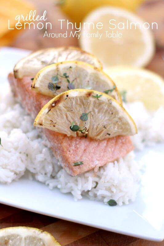 Grilled Lemon Thyme Salmon over a bed of rice on a plate with lemon slices.