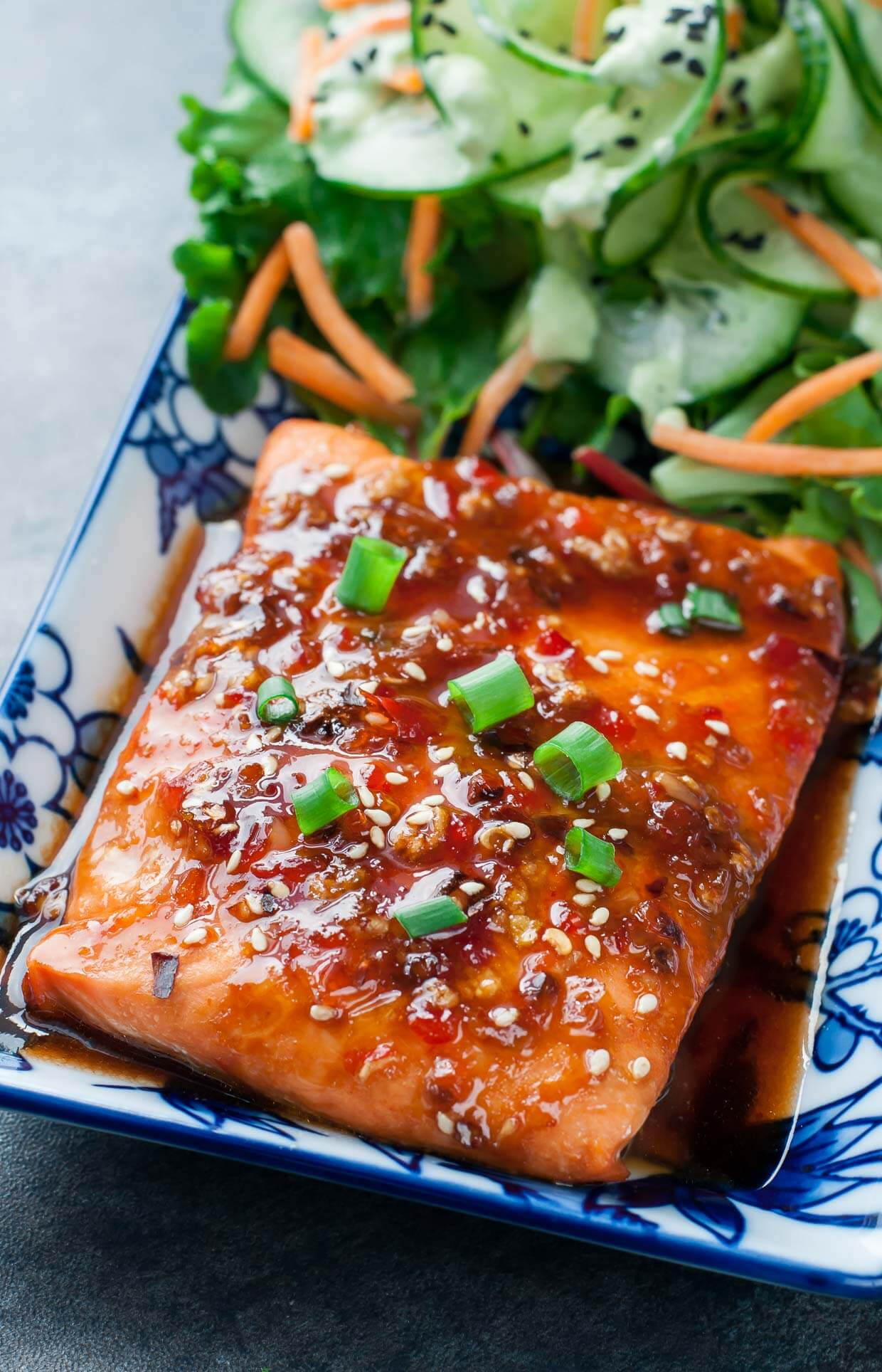 Sweet Chili Sriracha Salmon on a plate with fresh vegetables.