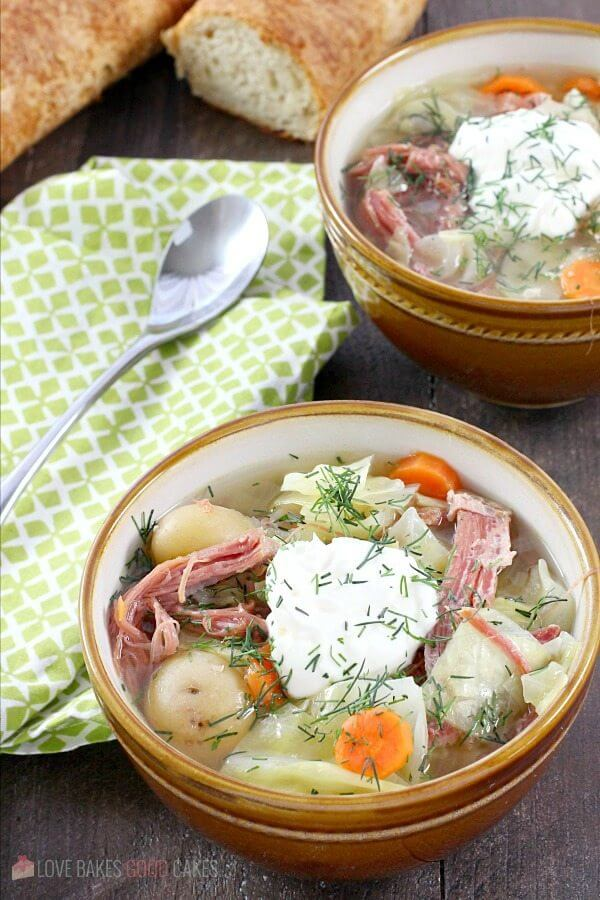Corned Beef and Cabbage Soup in two bowls with a spoon.