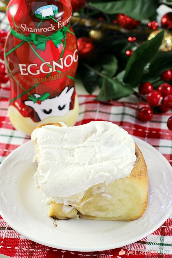 Eggnog Cinnamon Roll on a plate with a bottle of Eggnog close up.