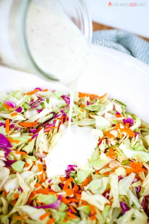 Dressing being poured onto homemade coleslaw.