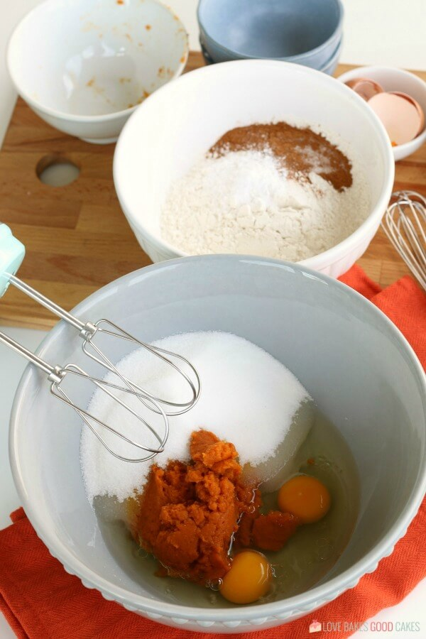 The ingredients for pumpkin muffins added to mixing bowls.