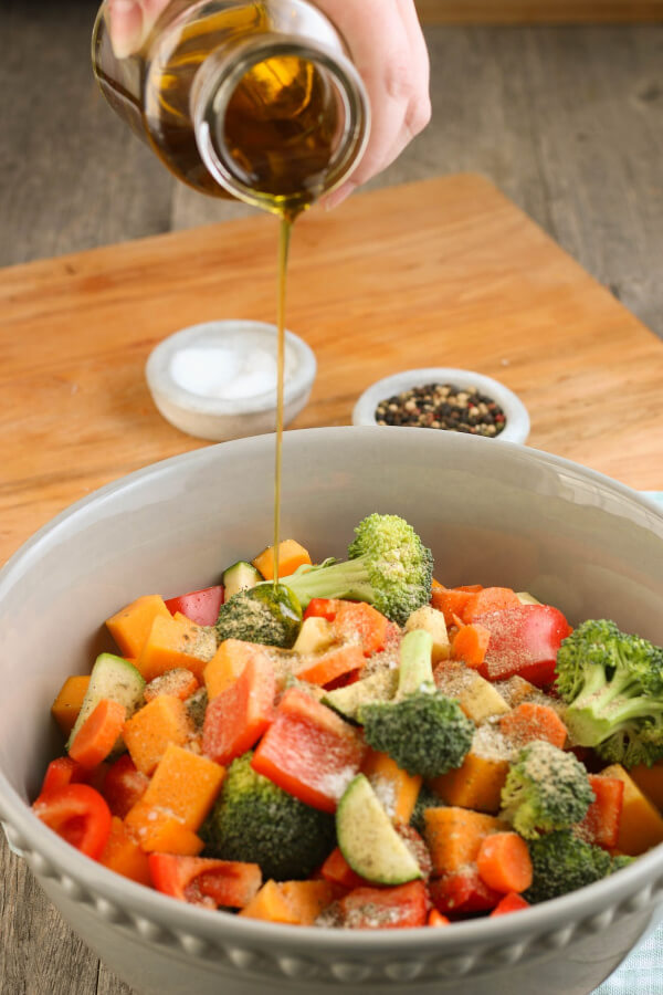 Adding olive oil to our chicken and vegetables helps the seasoning stick!