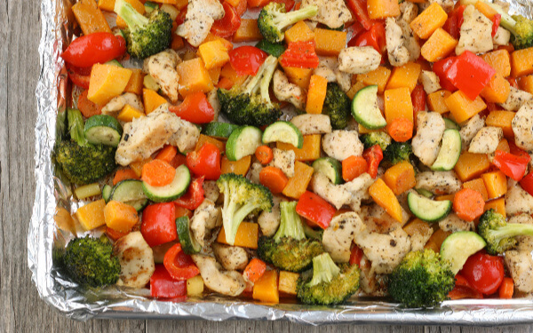 This is a horizontal view of the finished chicken and vegetables sheet pan meal.