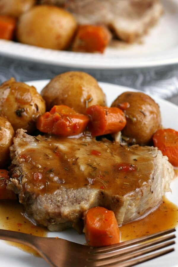 a serving of the pressure cooker pork roast on a plate with gravy and vegetables.