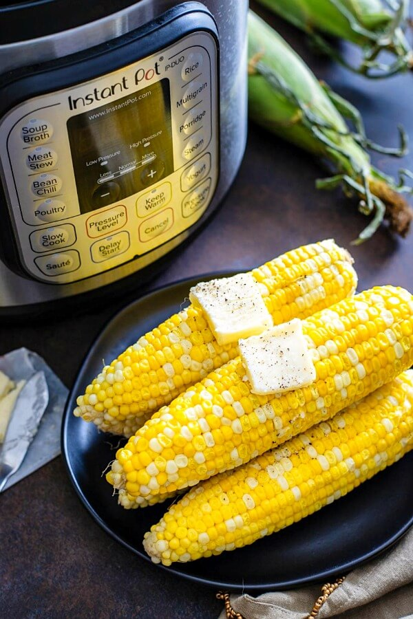 instant pot corn with butter on plate and pressure cooker in background