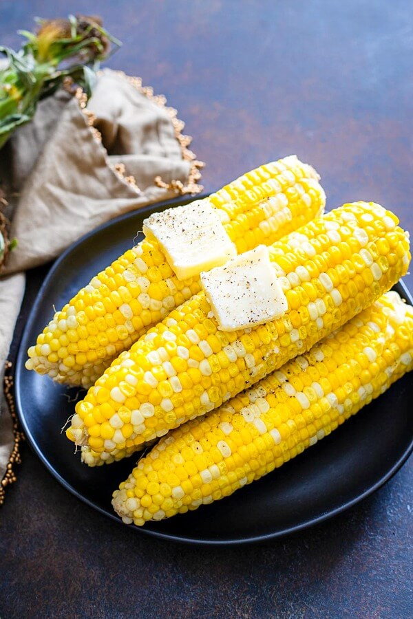 cooked ears of corn with butter on black plate