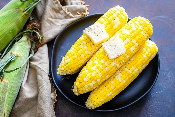 pressure cooked corn on the cob on a plate with butter