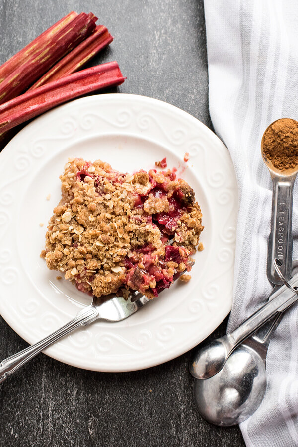 rhubarb crisp on plate with rhubarb and measuring spoon in background