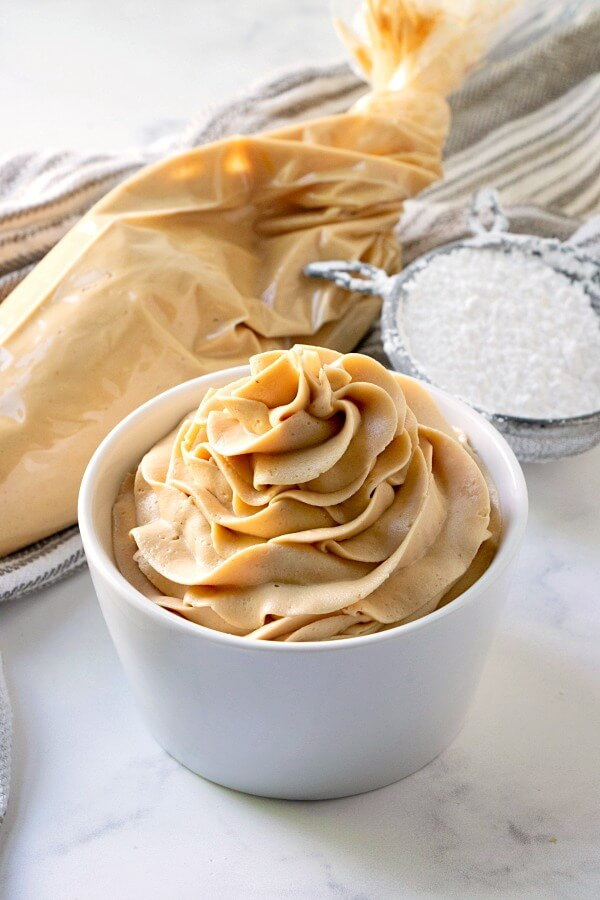 peanut butter frosting in small bowl and piping bag