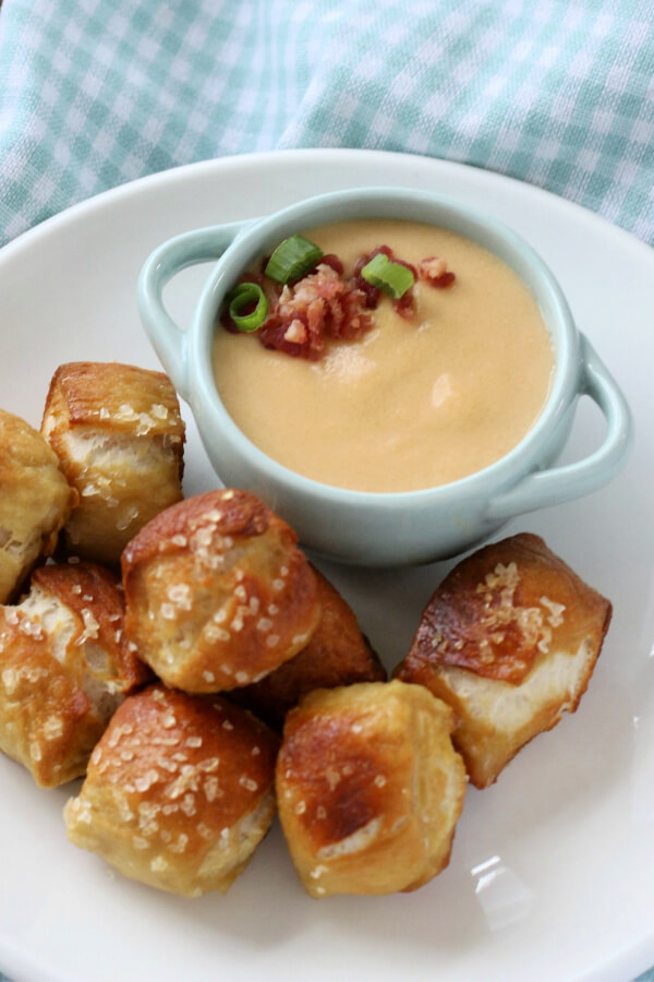 beer cheese dip in small bowl with pretzel bites on side