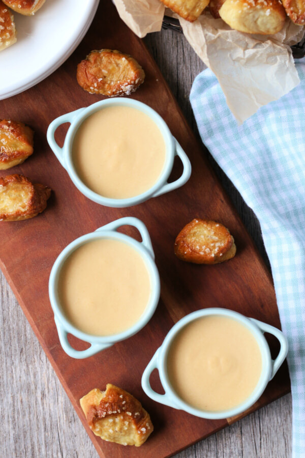 three small bowl of beer cheese dip with pretzel bites next to them