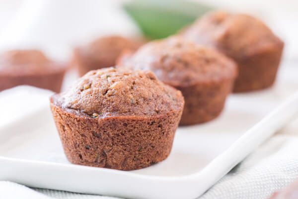 three zucchini muffins lined up on a diagonal on white plate
